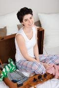 Young woman sitting in suitcase on bed Stock Photos