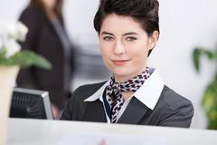 Confident young receptionist at reception Stock Photos