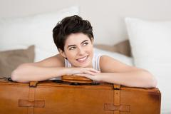 woman looking away while leaning on suitcase - stock photo