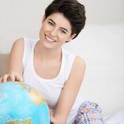 happy woman searching for travel destination on globe - stock photo