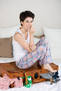Woman sitting on overloaded suitcase in bed Stock Photos