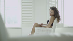 Beautiful brunette model sitting in a chair by the window Stock Footage