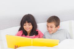 Stock Photo of Siblings in bed looking together at their photograph