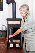 Senior lady puting wood in the stove Stock Photos