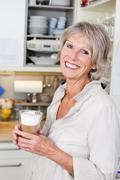 Elderly woman enjoying a cup of cappuccino Stock Photos