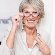 happy senior lady wearing reading glasses - stock photo