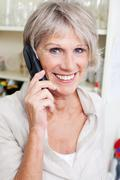 smiling senior lady talking on a telephone - stock photo