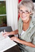 older woman wearing glasses working - stock photo