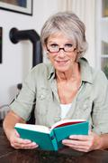 attractive elderly woman reading a book - stock photo