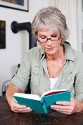 senior woman reading with reading glasses - stock photo