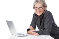Smiling senior woman using a laptop computer Stock Photos