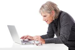 senior woman concentrating when using her laptop - stock photo