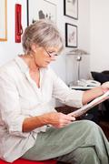 trendy senior woman reading a newspaper - stock photo