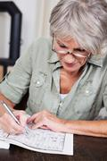 senior woman completing a crossword puzzle - stock photo