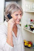 trendy older woman talking on the phone - stock photo