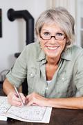 smiling elderly woman doing a crossword puzzle - stock photo