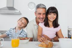 Siblings eating breakfast in kitchen together with dad - stock photo