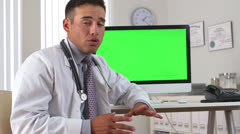 Hispanic doctor talking with green screen on computer in background Stock Footage