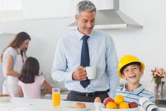 Funny little boy wearing fathers hardhat during breakfast - stock photo