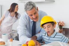 Father showing son his blueprints as he is wearing hardhat - stock photo