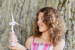 Girl looking at toy windmill against tree trunk Stock Photos