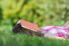 Sleeping girl with book on head Stock Photos