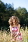 smiling girl walking through tall grass - stock photo