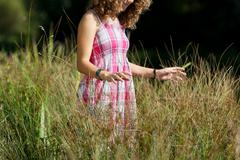 girl standing in tall grass at park - stock photo