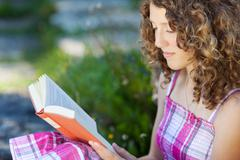 teenage girl with curly hair reading a book - stock photo