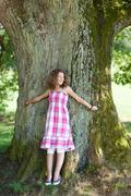 girl with curly hair stands in front of a tree - stock photo