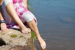 Low section of girl dipping foot in water Stock Photos