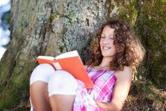 Girl reading book while leaning on tree trunk Stock Photos