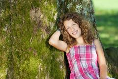 Girl leaning on tree trunk Stock Photos