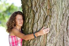 girl with eyes closed embracing tree - stock photo