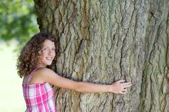 Girl with curly hair embracing a tree Stock Photos