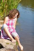 girl dipping foot in water - stock photo