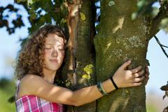 Young girl with eyes closed embracing tree Stock Photos
