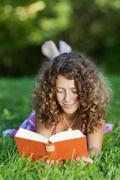 Girl reading book while lying on grass Stock Photos