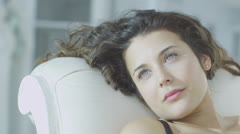 Beautiful model in lingerie reclines on a chaise and relaxes in the sunlight - stock footage