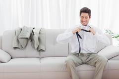 Smiling businessman sitting on sofa loosening his tie Stock Photos