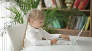 Stock Video Footage of Sweet liitle girl sitting at table with credit card in her hand using laptop