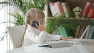 Stock Video Footage of Pretty little girl using laptop talking on mobile phone and looking at camera