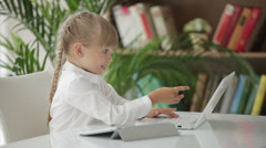 Cute little girl sitting at table with laptop turning around and smiling  Stock Footage