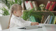 Stock Video Footage of Beautiful little girl sitting at table using laptop and touchpad and smiling