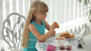 Stock Video Footage of Funny little girl sitting at table holding biscuit in her hand showing thumb