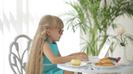 Stock Video Footage of Funny little girl wearing sunglasses sitting at table using laptop and eating