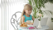 Stock Video Footage of Funny little girl sitting at table with plate of biscuits and cup of tea