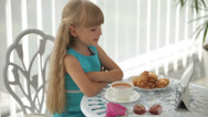 Stock Video Footage of Little girl sitting at table with plate of biscuits and cup of tea using tablet