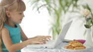 Stock Video Footage of Pretty little girl sitting at table laughing and using laptop