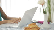 Stock Video Footage of Pretty little girl sitting at table using laptop and smiling happily at camera